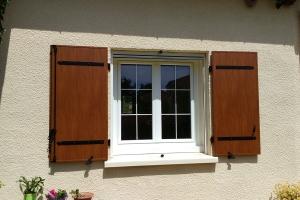 Fenêtre PVC avec petits bois incorporés dans le vitrage et volets battants en aluminium imitation bois