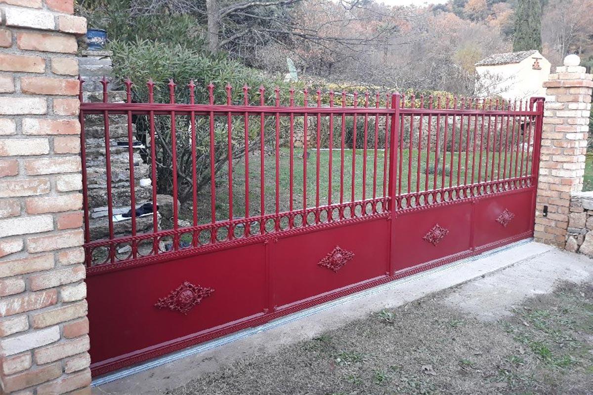 Portail coulissant motorisé en aluminium. Coloris rouge basque.