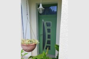 Porte d'entrée en aluminium. Blanche à l'intérieur vert RAL 6021 à l'extérieur. Modèle ENKO.