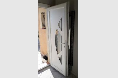 Porte d'entrée en pvc blanc. Panneau comportant une zone vitrée.