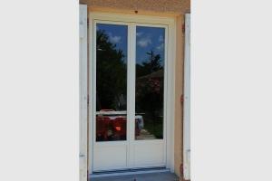 Porte-fenêtre en pvc blanc. Soubassement plein sur le bas de la porte.