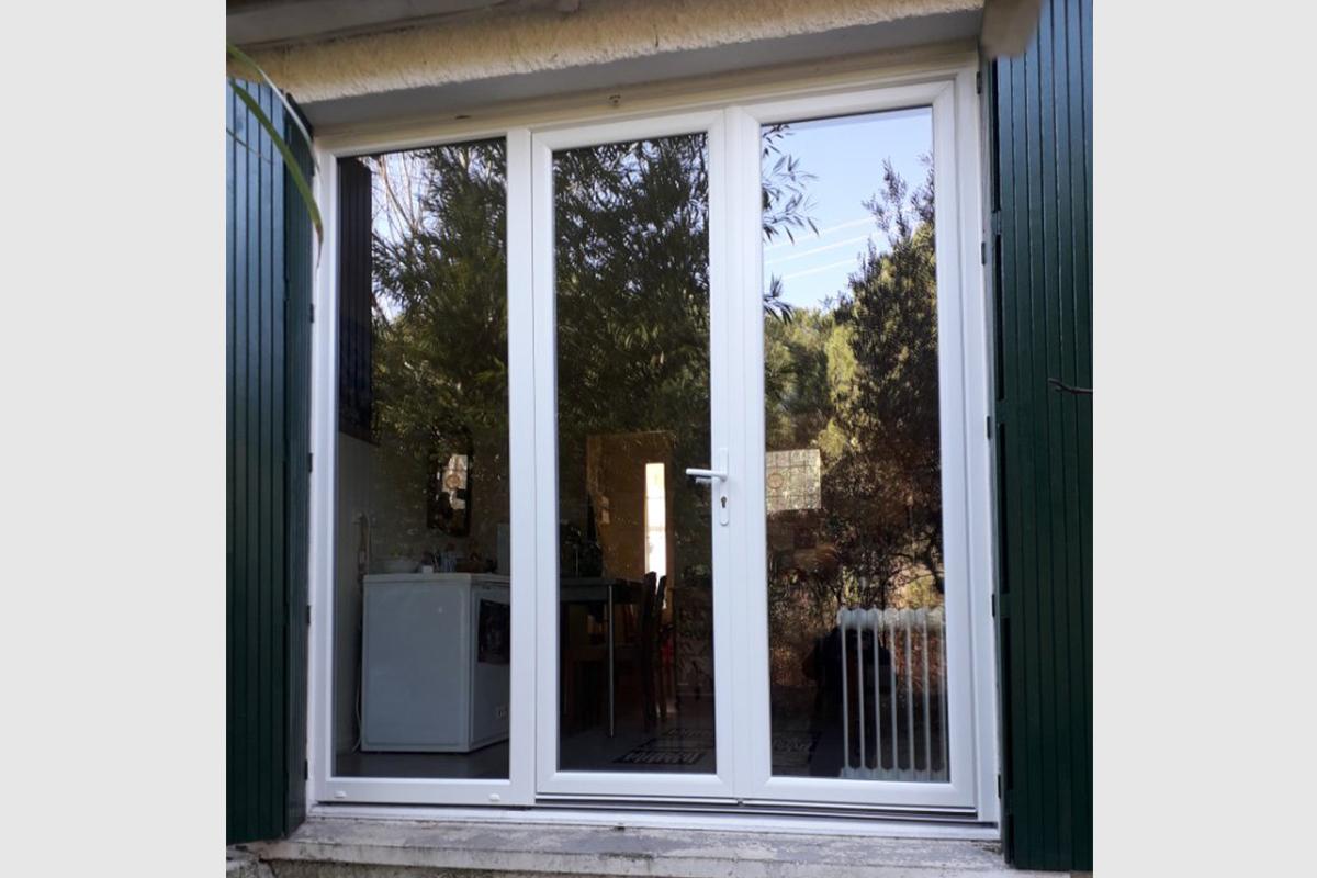 Porte-fenêtre en pvc blanc 3 vantaux dont un fixe. Vitrage jusqu'en bas de la porte.
