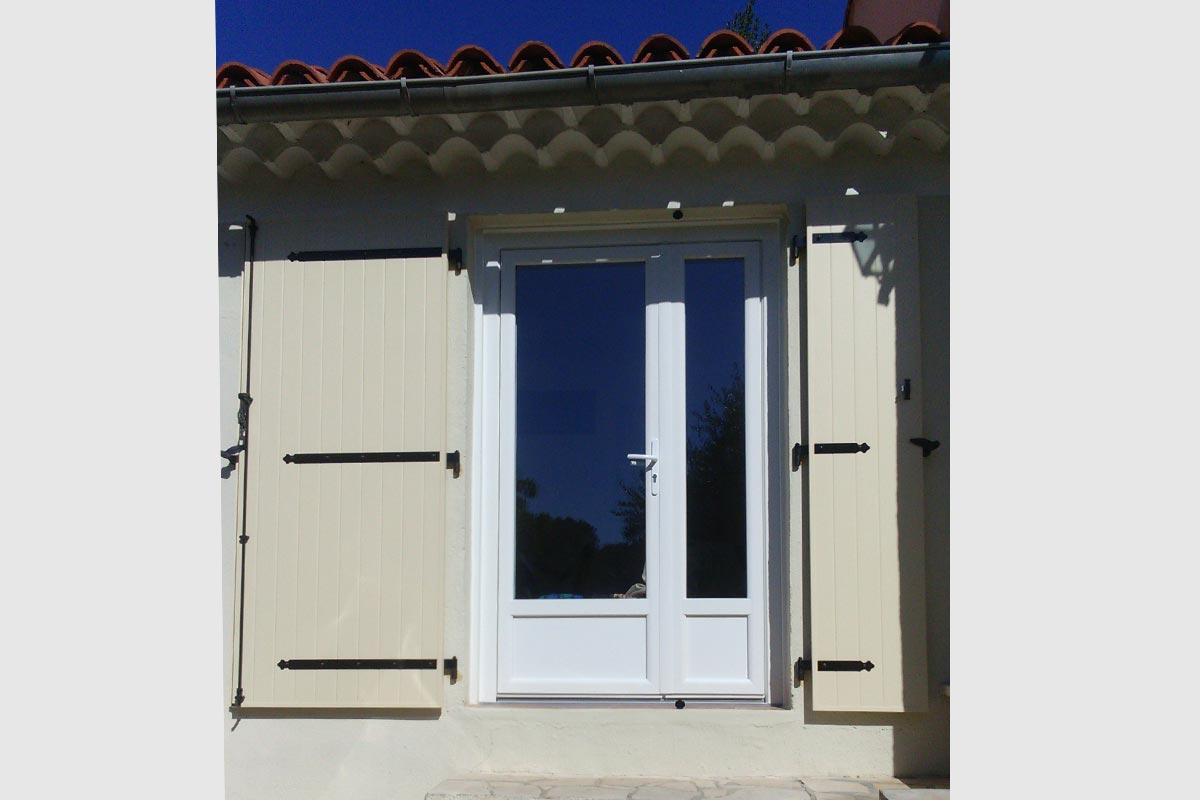 Volet battant en aluminium vantaux inégaux coloris ivoire RAL 1015. Porte-fenêtre tiercée blanche avec soubassement plein sur le bas.